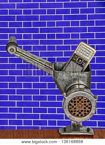 Old mobile phone in meat grinder on blue brick wall background taken closeup.