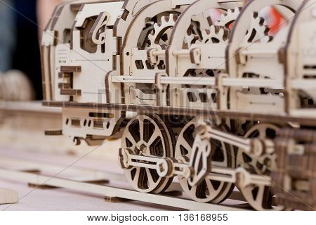 Selective focus on Children's wooden steam locomotive assembled from cut parts