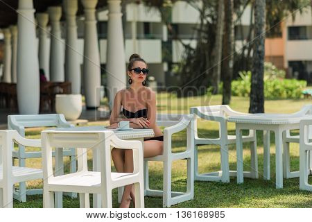 Sexy woman in bikini in Asia at beach cafe bar.Girl enjoying a cup of coffee outside. Smiling happy Caucasian woman near ocean beach. young beautiful woman relaxing on tropical vacation in Asia