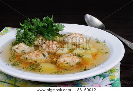 chicken broth of potatoes carrots and meatballs sprinkled with dill
