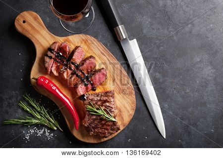 Grilled striploin sliced steak and red wine over stone table. Top view with copy space