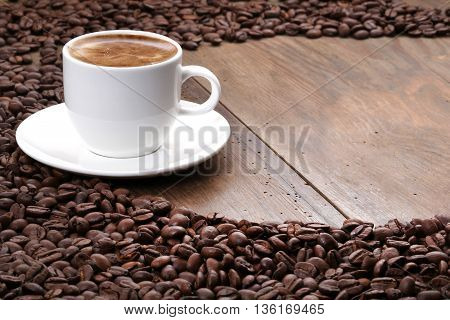 Coffee cup and coffee beans on a wooden table