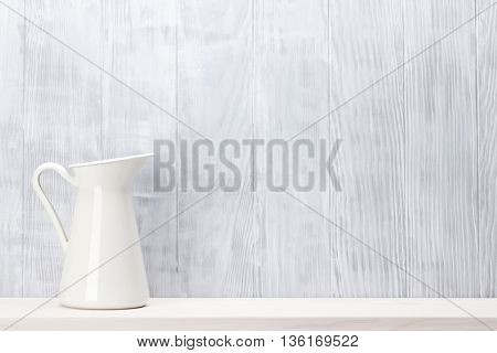 Pitcher on shelf in front of wooden wall. View with copy space