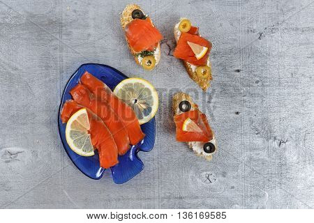 Tasty various italian sandwiches with seafood against rustic wooden background. Crostini with cheese red fish lemon and sliced olives horizontal top view