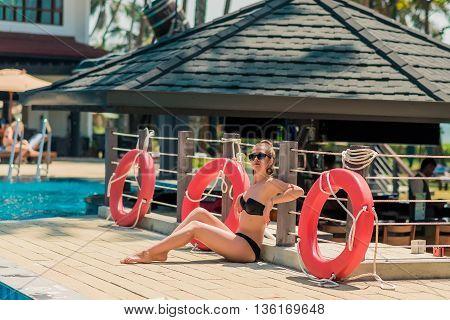 Sexy young curly woman relaxing near life-saving buoy. sexy girl in bikini seat near swimming pool. Woman sunbathing in bikini at tropical resort. Outdoor summer portrait of sexy girl