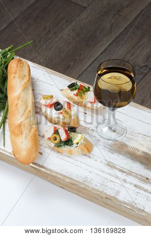 Tasty various italian sandwiches with seafood against rustic wooden background. Crostini with cheese crab sticks and olives bread and wine close up with selective focus