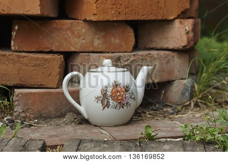 vintage tea pot near brick wall close up