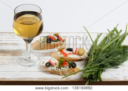 Tasty various italian sandwiches with seafood against rustic wooden background. Crostini with cheese crab sticks and olives on white plate bread herbs and wine close up with selective focus
