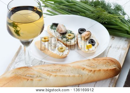 Tasty various italian sandwiches with seafood against rustic wooden background. Crostini with cheese mussels and olives on white plate bread herbs and wine close up with selective focus