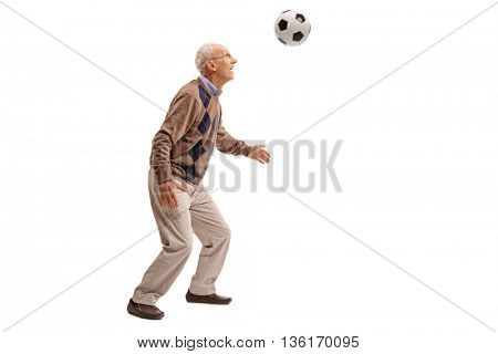 Studio shot of a senior man heading a football isolated on white background