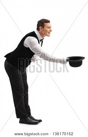 Full length profile shot of a young male waiter bow down and taking off his hat isolated on white background