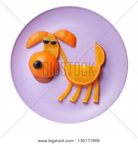 Dog made of oranges on pink plate