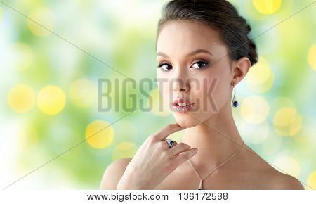 beauty, jewelry, people and luxury concept - beautiful asian woman or bride with earring, finger ring and pendant over summer green lights background