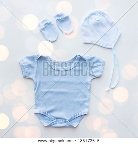 baby clothes, babyhood, motherhood and object concept - close up of blue bodysuit, hat and mittens for newborn boy on table