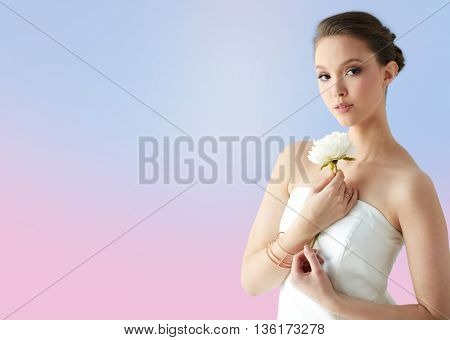 beauty, jewelry, people and luxury concept - beautiful asian woman or bride in white dress with peony flower, golden ring and bracelet over rose quartz and serenity gradient background
