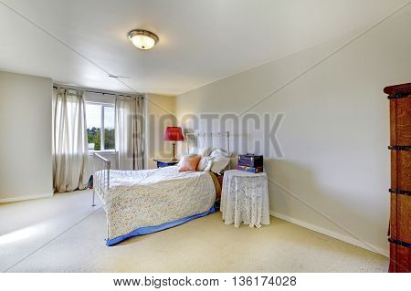 Ivory Wall Bedroom With White Iron Bed And Red Lamp On The Nightstand.