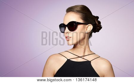 accessories, eyewear, fashion, people and luxury concept - beautiful young woman in elegant black sunglasses over violet background