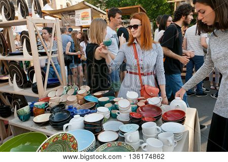 KYIV, UKRAINE - JUN 4, 2016: Young women choosing pottery on the stand of crowded weekend street fair on June 4, 2016. Kiev is the 8th most populous city in Europe.