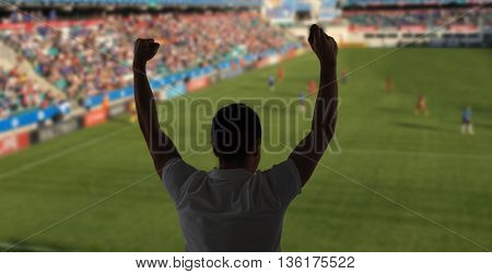 leisure, sport, entertainment and people concept - man watching soccer of football game and supporting team over stadium background