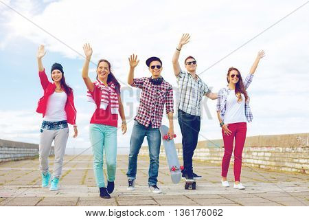 summer holidays and teenage concept - group of smiling teenagers waving hands outside