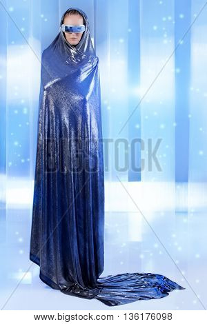Full length portrait of a magnifiscent  young woman in silver latex costume over futuristic background. Sci-fi style.