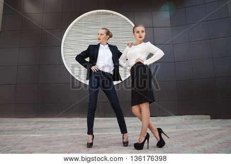 Blonde businesswomen in official clothes against of building facade