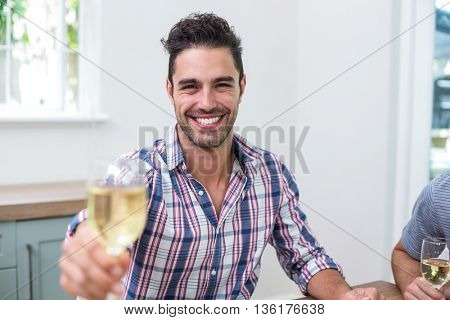 Portrait of handsome young man showing wineglass while sitting in house