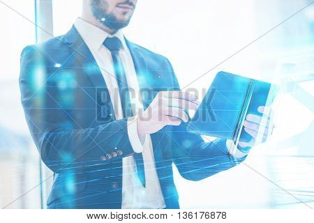 Businessman holding tablet in his hands against the window, in the blue shade.