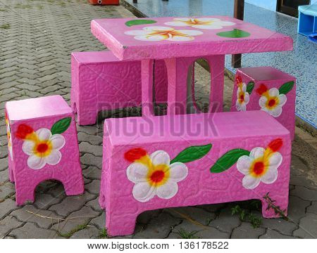 colorful pink, flowered concrete table and four seats at kindergarten near Ranot, Thailand