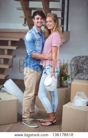 Portrait of smiling romantic couple while standing in new house
