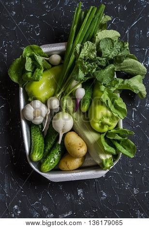 Fresh green and white vegetables - cucumbers peppers radish radish garlic onion potato on a dark background. Healthy vegetarian food