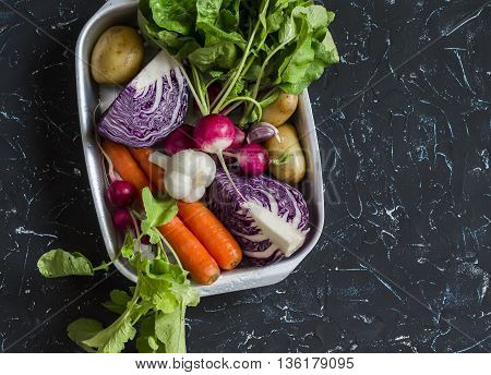 Fresh vegetables - red cabbage radishes carrots potatoes garlic onions on a dark stone background. Healthy vegetarian diet detox food. Top view