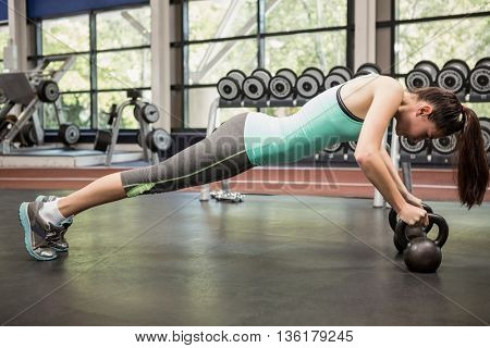 Woman working out with kettlebell at gym