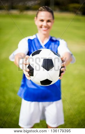 Female football player standing in field with a ball