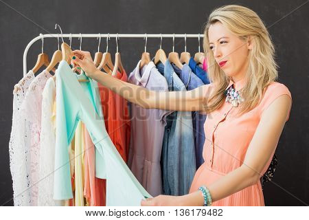 Woman looking at piece of clothing and making a decision
