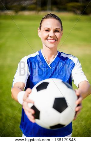 Portrait of female football player standing in field with a ball