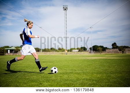 Female football player practicing soccer in a stadium