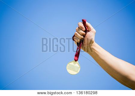 Close-up of athlete hand holding gold medal against sky