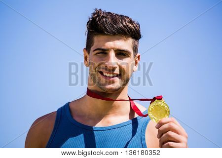Happy athlete showing his gold medal