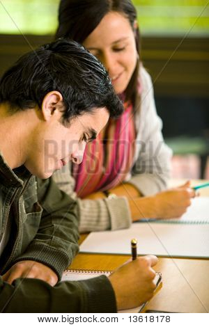 students in a library making notes on a notebook