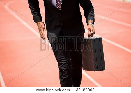 Mid section of businessman with briefcase running on a running track