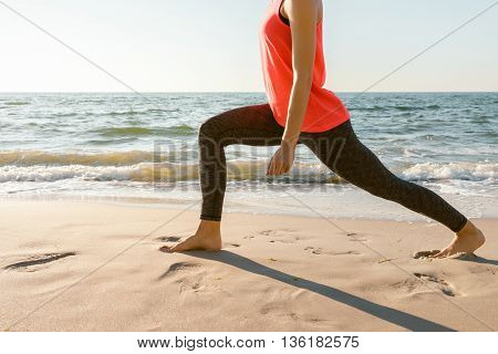 Slim athletic woman in a red shirt engaged stretching barefoot on the beach in the morning sunlight. Concept sports lifestyle.