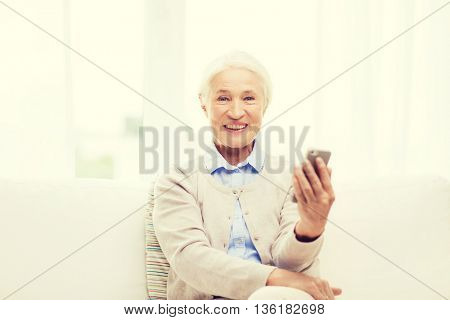 technology, communication age and people concept - happy senior woman with smartphone at home