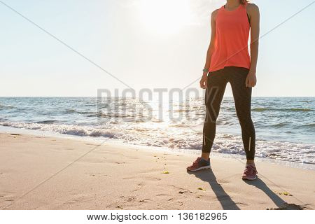 Athletic woman in red T-shirt without sleeves and sneakers standing on the beach in the morning sunshine before jogging. Concept sports lifestyle space for text.