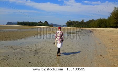 young woman walking up beach at low tide, Ao Nung, Thailand