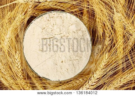bowl of flour surrounded by wheat ears