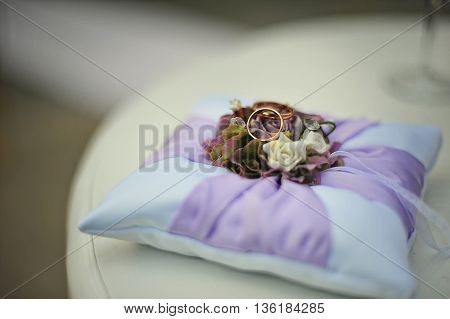 Purple pillow with wedding rings  at wedding