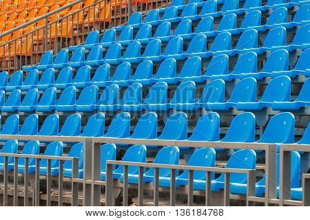 Rows of blue and orange chairs on a soccer stadium