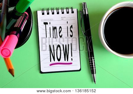 The words Time is Now on notebook