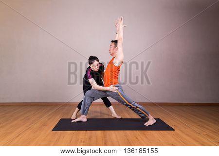Yoga Instructor Correcting Student Performing Warrior 1 Or Virabhadrasana 1